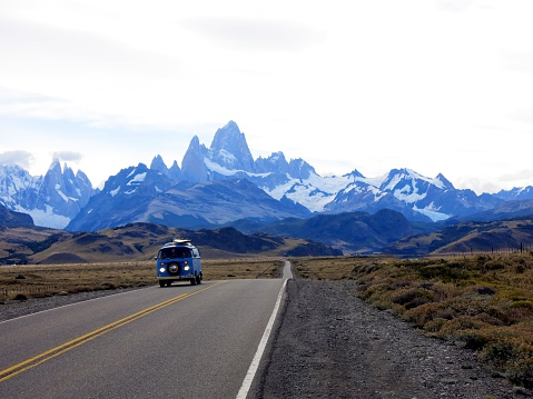 El Chalten, Los Glaciares National Park, Argentina - Febuary 12, 2016:A blue VW bus driving away from the silhouette of Fitz-Roy and Cerro Torre in the Los Glaciares National Park in Argentina