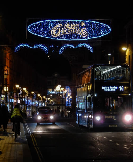 buses and cars pass under the christmas decorations along station road - john lewis стоковые фото и изображения