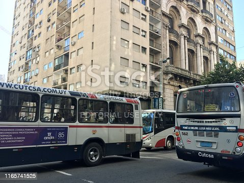 Montevideo, Uruguay - May 16, 2019: Buses moving in avenue in the city downtown. The city has a very good public transportation network that allows to reach almost any place in it