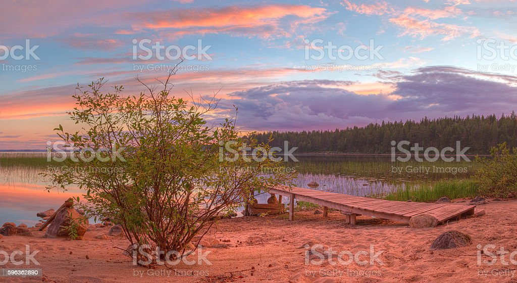 Bush and pier on shore of lake in beautiful evening royalty-free stock photo