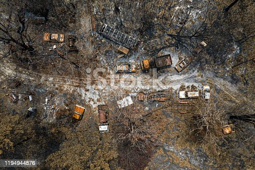Aerial view of Australian bush fire destruction with burnt vehicles, and property.