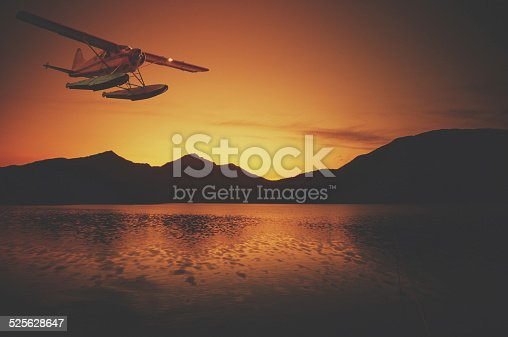 A float plane flies in dusk light over mountains in Southern Alaska.