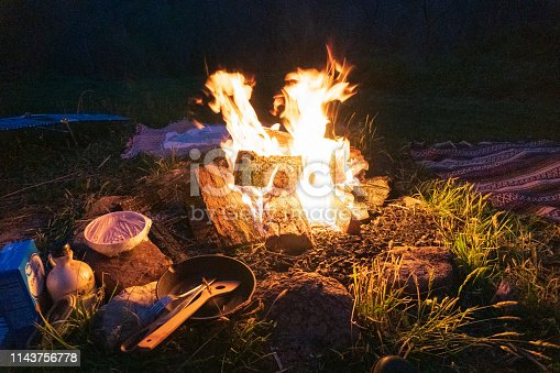 istock Bushcraft Campfire, Cast Iron Skillet, Camp Blankets and spatula at night. Pristine bon fire cooking in the Blue Ridge Mountains in Asheville, North Carolina. 1143756778