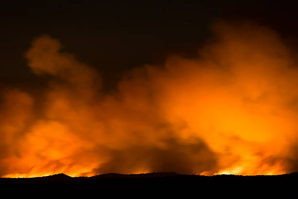 Bushfire, flames and smoke over the horizon, copy space Bushfire, back burning at night in Blue Mountains Australia, flames and smoke over the horizon, full frame horizontal composition with copy space smoke jumper stock pictures, royalty-free photos & images