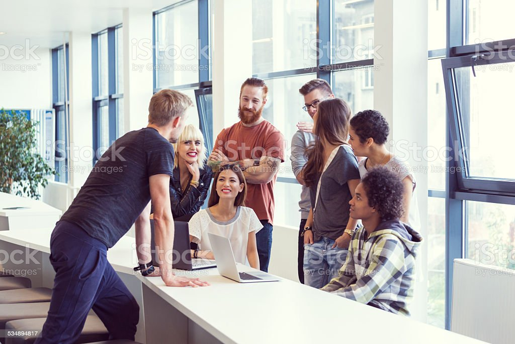 Busienss team brainstorming in an office Multi ethnic business team having meeting in an office and listening to their leader.  2015 Stock Photo