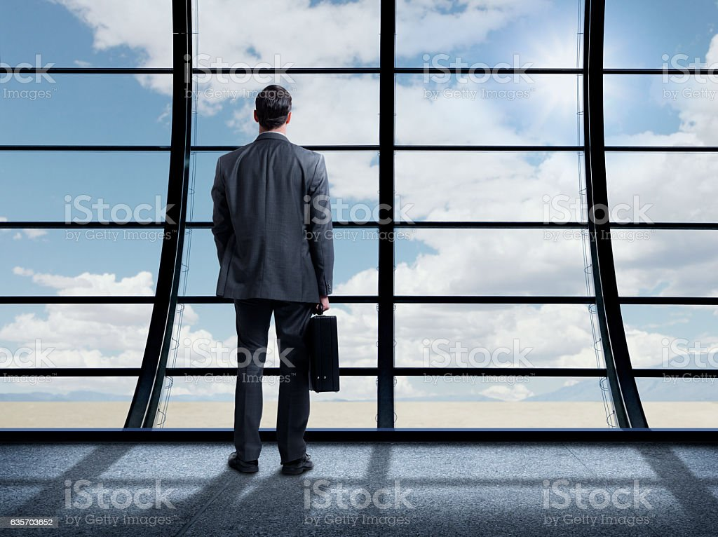 Busienssman Standing Inside Office Building Looking Out Large Window royalty-free stock photo