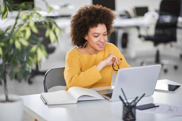 Busiensswoman schaut auf Laptop, während sie im modernen Büro sitzt. – Foto