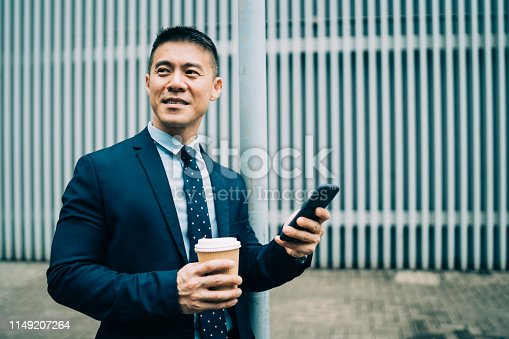 Busiessman holding coffee cup and smart phone on street.
