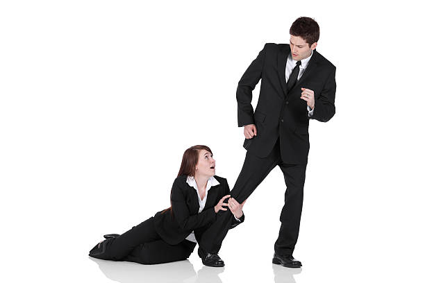 Busiesswoman holding the leg of a businessman stock photo