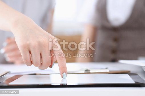 1063657732 istock photo Businees woman toch on tablet pc finger display 877384272