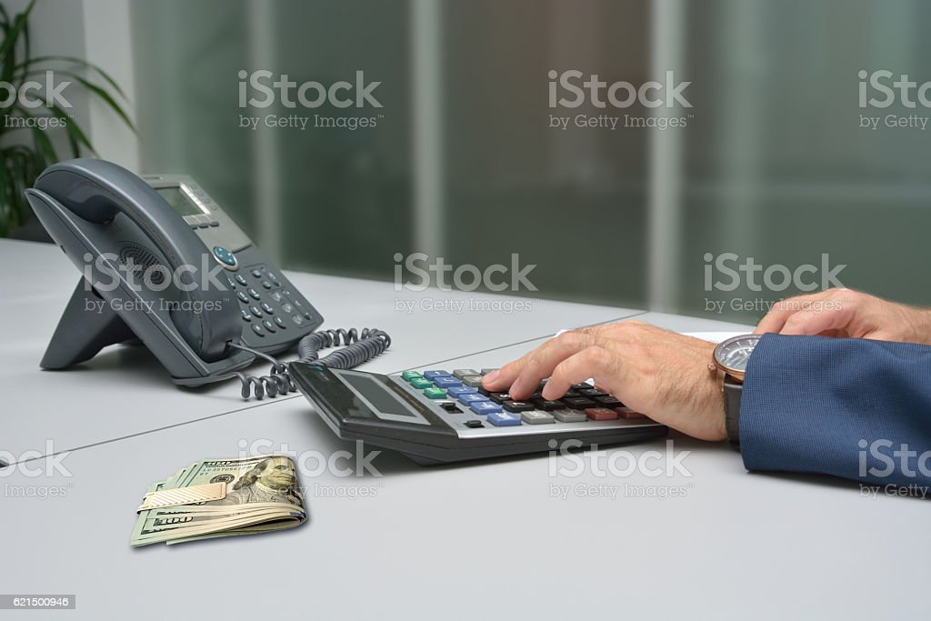 Businesman counting on calculator at the office photo libre de droits
