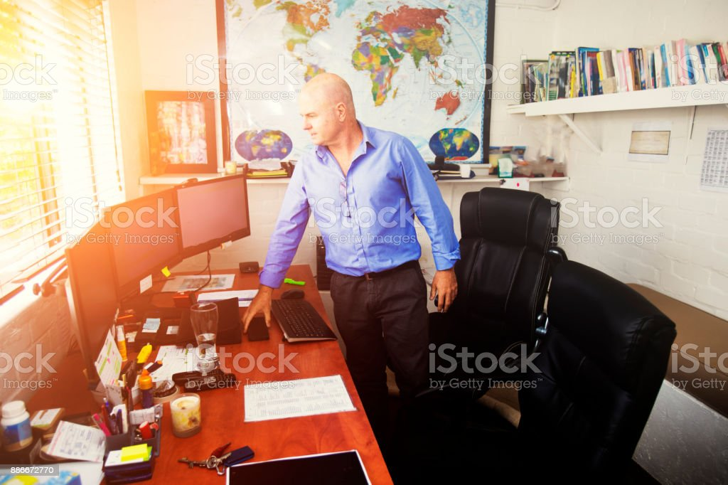 Businesman stands in his messy office looking at the  computer monitor stock photo