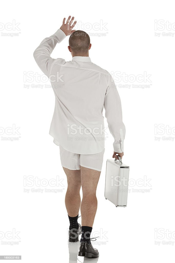 Businesman without pants carrying a suitcase stock photo
