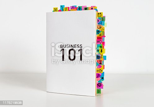 Business 101 book and sticky reminders on the white background. Elementary book.