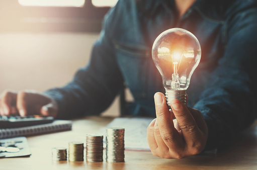 istock business accountin with saving money with hand holding lightbulb concept financial background 820374558