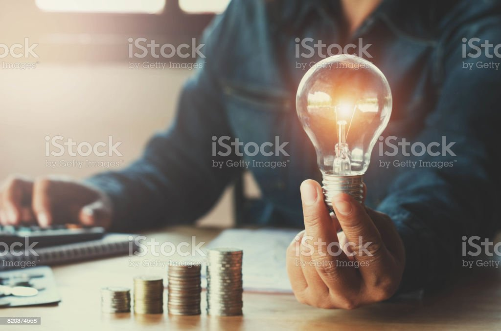 business accountin with saving money with hand holding lightbulb concept financial background stock photo