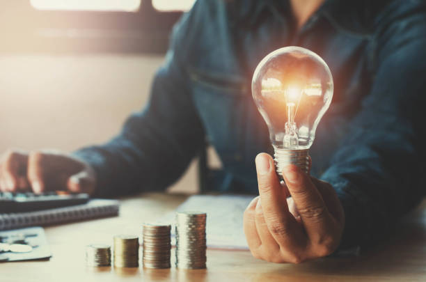 business accountin with saving money with hand holding lightbulb concept financial background - światło led zdjęcia i obrazy z banku zdjęć