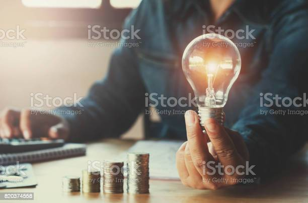 Business Accountin With Saving Money With Hand Holding Lightbulb Concept Financial Background Stock Photo - Download Image Now