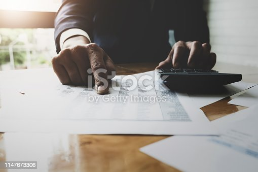 istock Business accounting , Business man using calculator with calculate stock maket data chart, tax and budget paper in office.  accounting auditor concepts. 1147673306