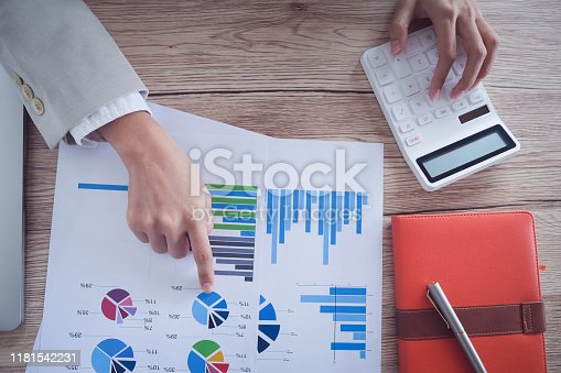 941729686 istock photo Business accounting concept, Business man pen pointing chart and using calculator to calculating budget and loan paper in office. 1181542231