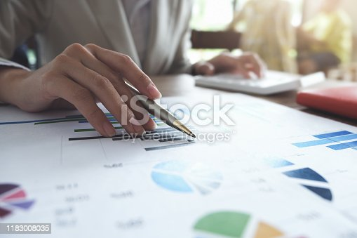 941729686 istock photo Business accounting concept, Business man pen pointing chart and using calculator to calculating budget and loan paper in office. 1183008035