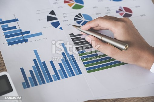 941729686 istock photo Business accounting concept, Business man pen pointing chart and using calculator to calculating budget and loan paper in office. 1183008083