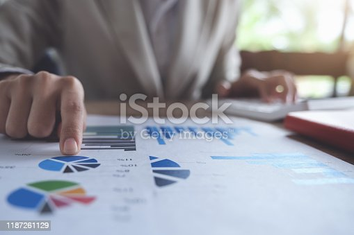 941729686 istock photo Business accounting concept, Business man pointing graph chart and using calculator to calculating budget and loan paper in office. 1187261129