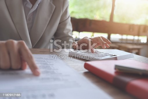 941729686 istock photo Business accounting concept, Business man using calculator to calculating budget and loan paper in office. 1182912165
