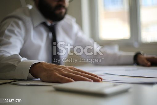 941729686 istock photo Business accounting concept, Business man using calculator with computer laptop, budget and loan paper in office. 1251371752