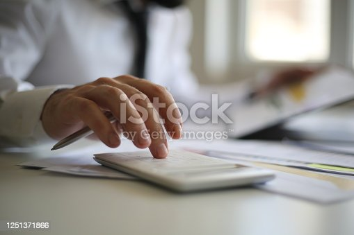 941729686 istock photo Business accounting concept, Business man using calculator with computer laptop, budget and loan paper in office. 1251371866