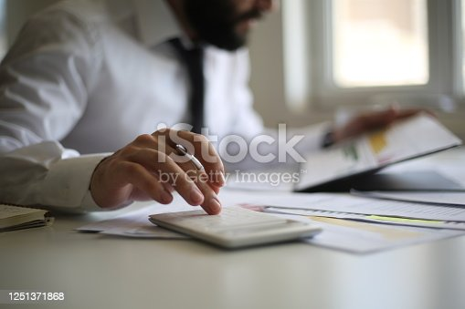 941729686 istock photo Business accounting concept, Business man using calculator with computer laptop, budget and loan paper in office. 1251371868
