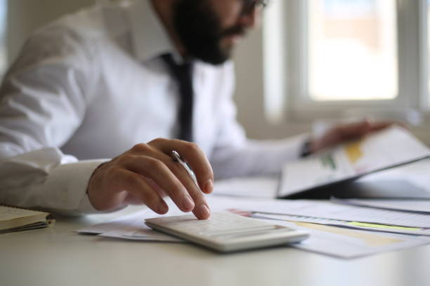 Business accounting concept, Business man using calculator with computer laptop, budget and loan paper in office. stock photo