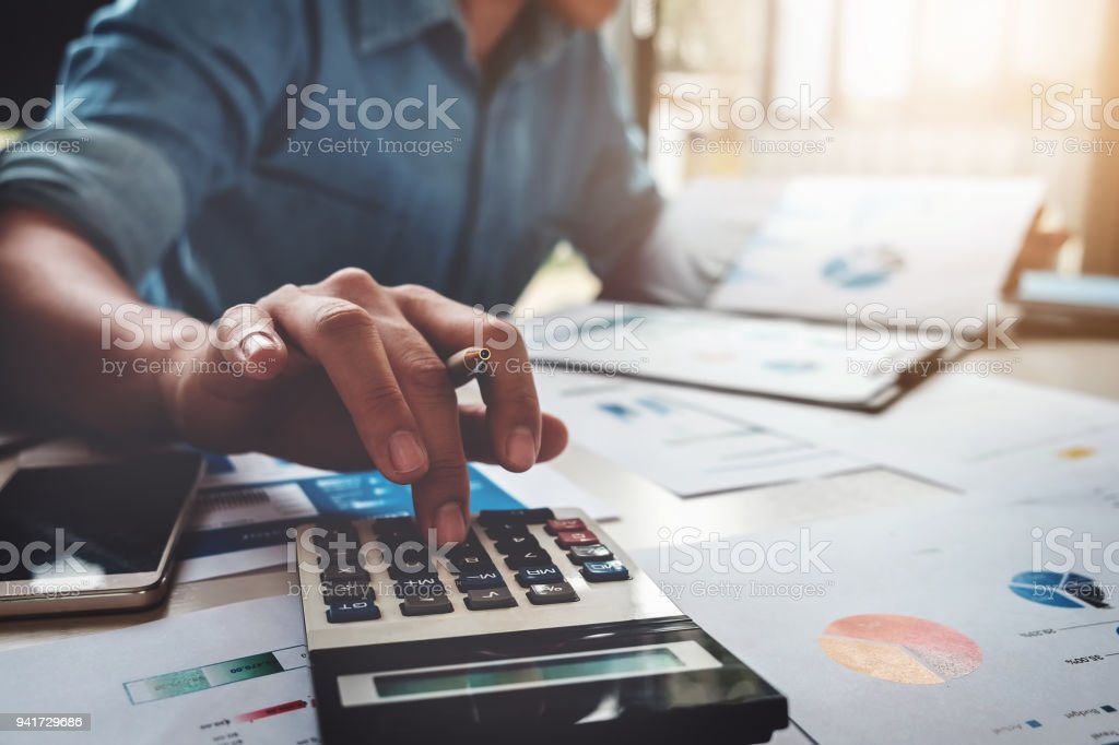 Business accounting concept, Business man using calculator with computer laptop, budget and loan paper in office. - Foto stock royalty-free di Adulto