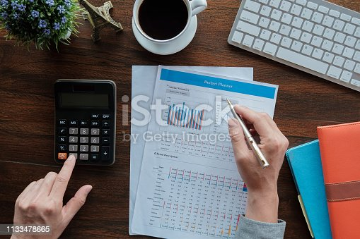istock Business accounting concept, Business man using pen pointing  with stock maket data financial chart and calculator for calculate budget planner  paper in office. 1133478665