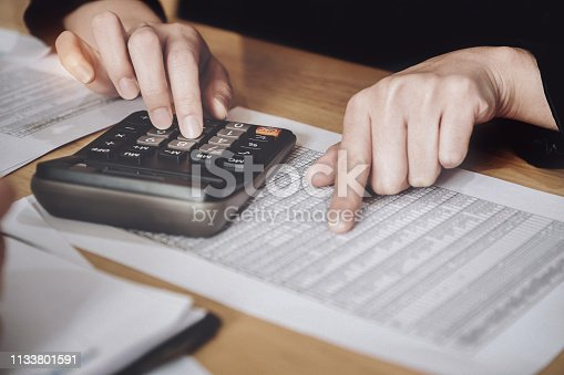 istock Business accounting concept, Business woman using calculator with stock marketing data chart, budget and loan paper in office. 1133801591