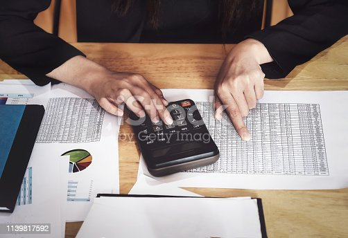 istock Business accounting concept, Business woman using calculator with stock marketing data chart, budget and loan paper in office. 1139817592