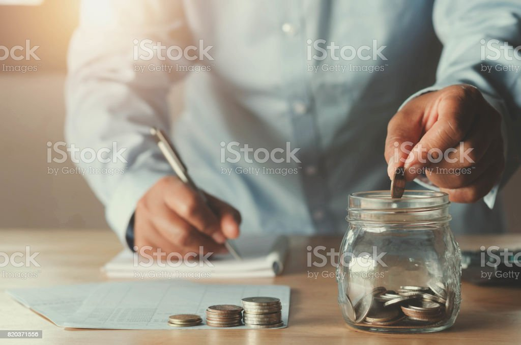 business accounting with saving money with hand putting coins in jug glass concept financial stock photo