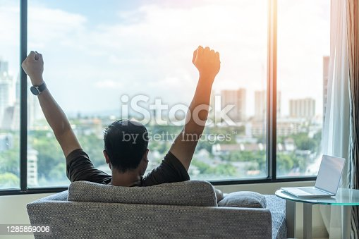 Business achievement concept with happy businessman relaxing in home office or hotel room, resting and raising fists with ambition looking forward to city building urban scene
