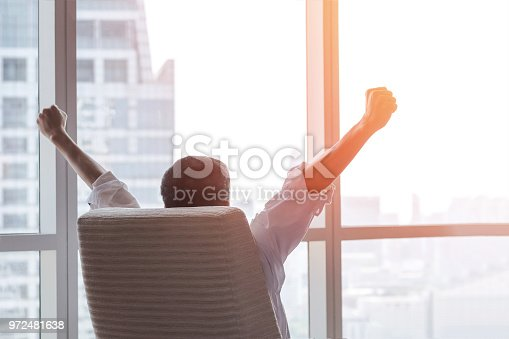 istock Business achievement concept with happy businessman relaxing in office room, resting and raising fists with ambition looking forward to city building urban scene through glass window 972481638