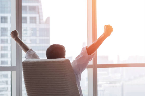 Business achievement concept with happy businessman relaxing in office room, resting and raising fists with ambition looking forward to city building urban scene through glass window stock photo