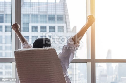 istock Business achievement concept with happy businessman relaxing in office room, resting and raising fists with ambition looking forward to city building urban scene through glass window 995745318