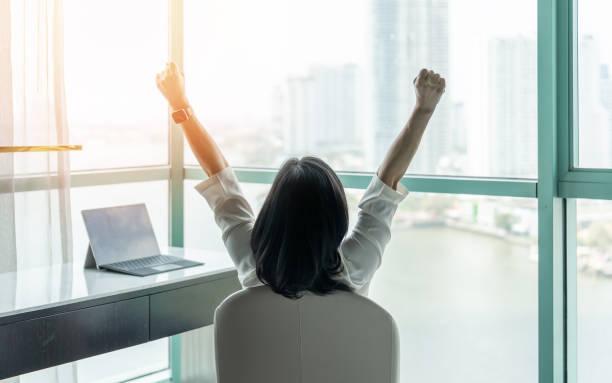 商業成就理念,快樂的女商人在辦公室或酒店房間放鬆,休息和舉起拳頭與野心期待城市建設城市場景通過玻璃視窗 - 成功 個照片及圖片檔