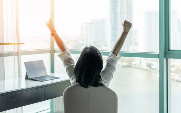 Business achievement concept with happy businesswoman relaxing in office or hotel room, resting and raising fists with ambition looking forward to city building urban scene through glass window stock photo