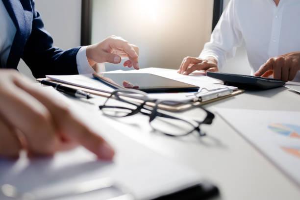 business administrator negotiation discussing  about investment data spreadsheets in modern office. - wnętrze zdjęcia i obrazy z banku zdjęć
