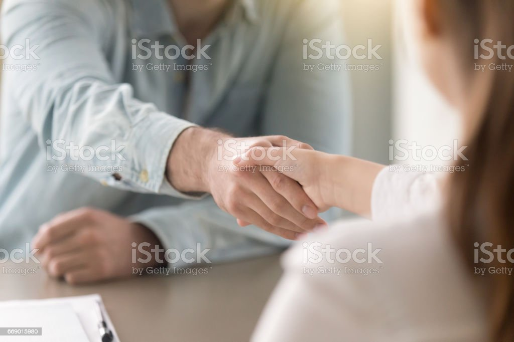 Business agreement handshake of man and woman at the office Businessman shaking female hand above the table. Business agreement and partnership concept. Partners closing a deal, view over the shoulder. Formal greeting gesture, effective negotiations 20-29 Years Stock Photo