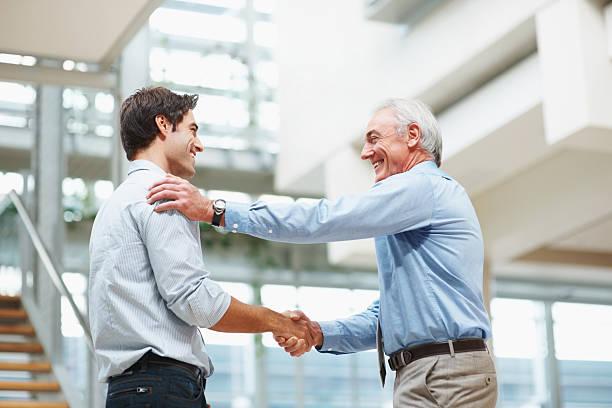 contrat d'affaires senior et jeunes hommes d'affaires se serrant la main - admiration photos et images de collection