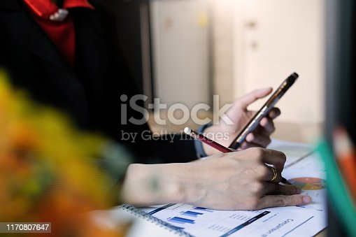 897852992istockphoto Business analysis. Businesswoman holding pencil, using mobile phone consulting colleagues, working on laptop computer reviewing business marketing financial report on desk in modern office. 1170807647