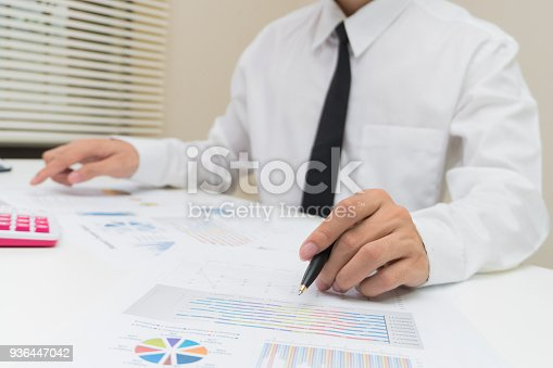 858031152istockphoto Business and finance concept : Businessman check about cost and doing finance graph report at office, Finance managers task,Businessman recheck new plan financial graph data. 936447042