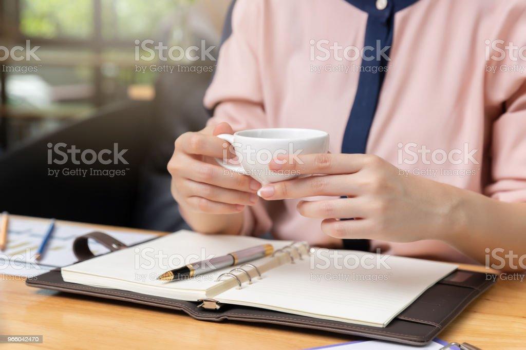 Företag och finans konceptet, affärskvinna håller kaffekoppen och diskutera försäljning analys diagram i kafé - Royaltyfri Affärskvinna Bildbanksbilder
