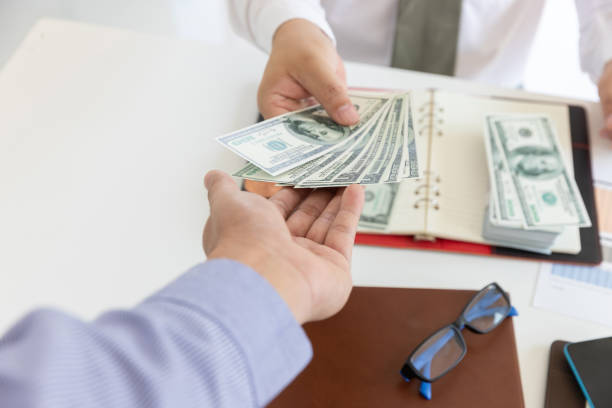 Business and finance concept, Hand of a businessman giving money to his partner. Business and finance concept, Hand of a businessman giving money to his partner. loan stock pictures, royalty-free photos & images